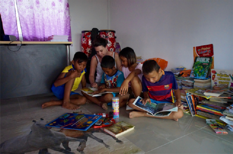 A girl reads book to children